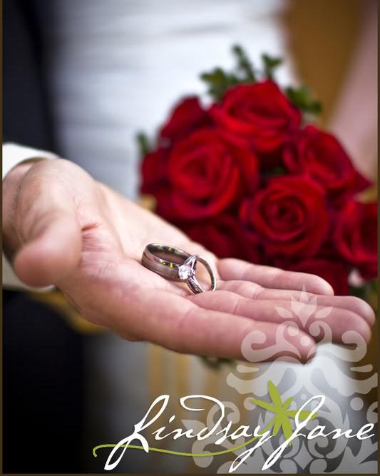 A groom holds LDS wedding rings
