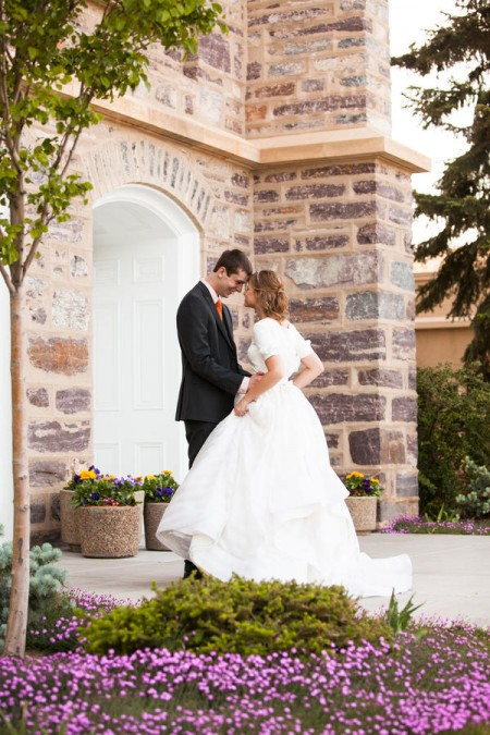 An LDS bride in her modest wedding dress with her groom