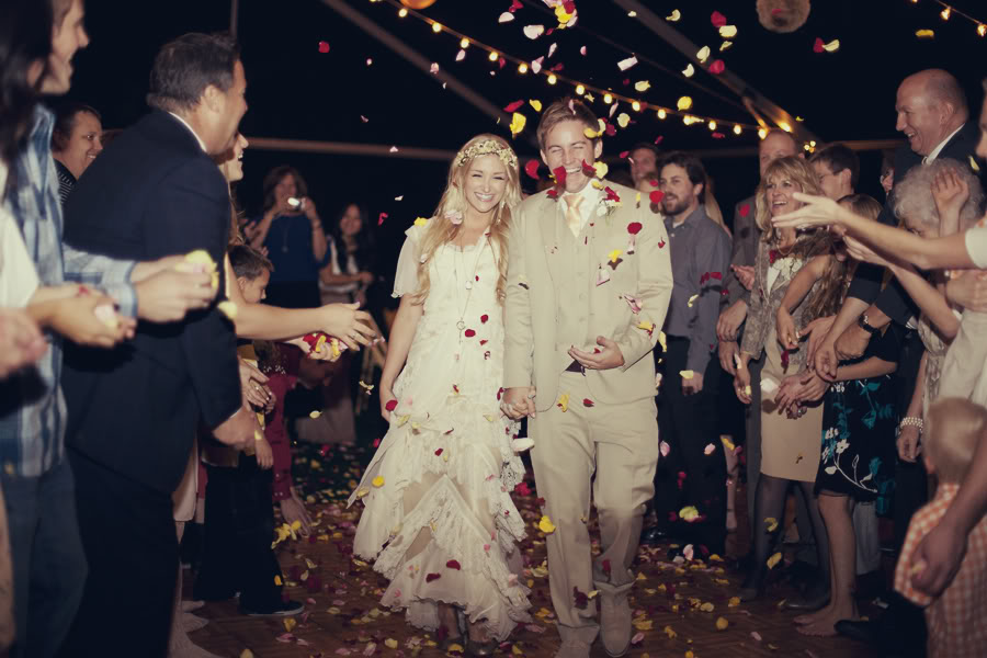 An LDS bride and groom exit the wedding reception to rose petals being thrown for good luck