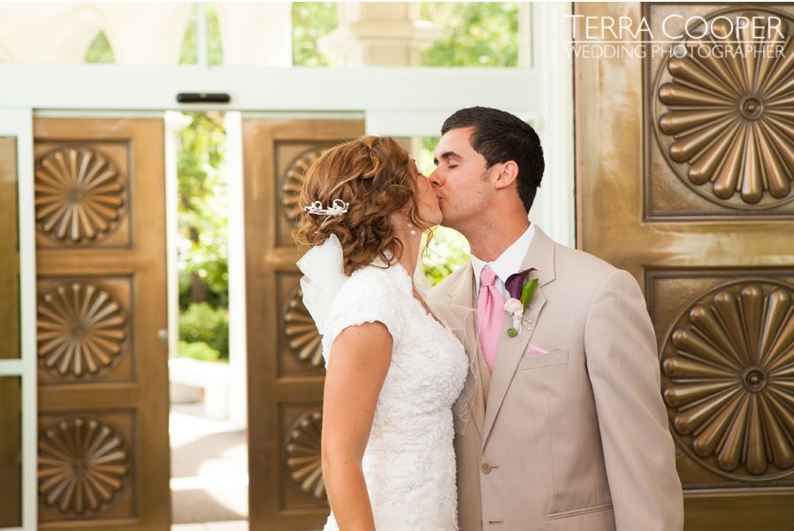 An LDS bride and groom share a passionate kiss outside the LDS Temple