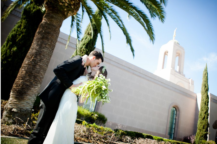 An LDS bride and groom share a kiss outside the LDS Temple, WeddingLDS.com